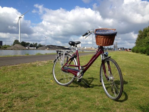 Bike next to a canal with wind turbine in the background