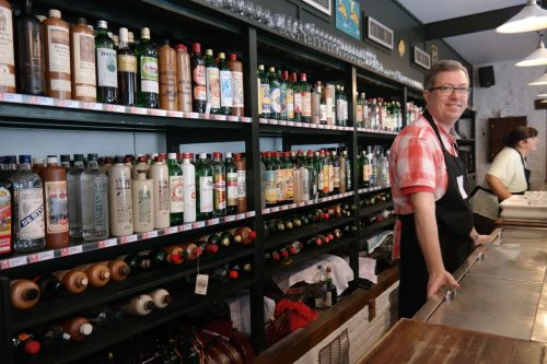 Man standing behind a bar with a large selection of jenever bottles behind him